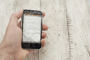 Mid adult man holding broken cellphone, close upの写真素材 [FYI04337538]