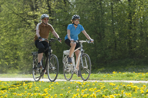 Germany, Bavaria, Munich, Man and woman riding electric bicyの写真素材 [FYI04337558]