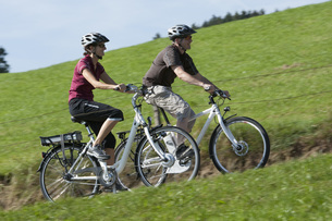 Germany, Bavaria, Man and woman riding electric bicycleの写真素材 [FYI04337560]