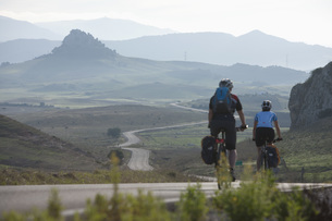 Spain, Andalusia,  Man and woman cycling through country roaの写真素材 [FYI04337567]
