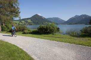 Germany, Bavaria, Man cycling through country roadの写真素材 [FYI04337573]
