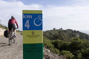 Spain, Mallorca, Woman cycling, road sign in foregroundの写真素材 [FYI04337582]