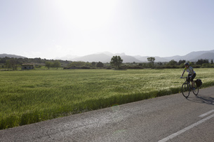 Spain, Mallorca, Woman cycling through country roadの写真素材 [FYI04337585]