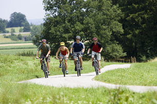 Germany, Bavaria, Oberland, Four mountainbikers riding acrosの写真素材 [FYI04337603]