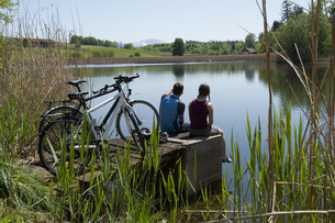 Germany, Bavaria, Man and woman sitting by bicycleの写真素材 [FYI04337607]