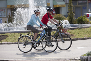 Italy, Trento, Man and woman cycling by fountain in Arcoの写真素材 [FYI04337608]