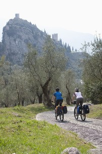 Italy, Trento, Man and woman cycling, Castle of Arco in backの写真素材 [FYI04337609]