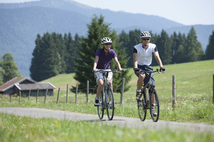 Germany, Bavaria, Man and woman cycling through country roadの写真素材 [FYI04337610]