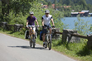 Germany, Bavaria, Man and woman cycling by Lake Walchenseeの写真素材 [FYI04337611]