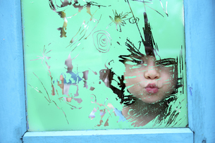 Girl looking through the glass of an old windowの写真素材 [FYI04337722]