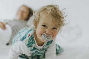 Portrait of happy little girl with mother in bedの写真素材 [FYI04337805]