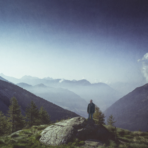 Italy, Lombardy, Chiesa in Valmalenco, man standing on a rocの写真素材 [FYI04337859]