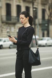 Spain, Catalunya, Barcelona, young black dressed businesswomの写真素材 [FYI04337903]