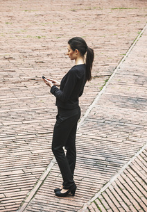 Spain, Catalunya, Barcelona, young black dressed businesswomの写真素材 [FYI04337908]