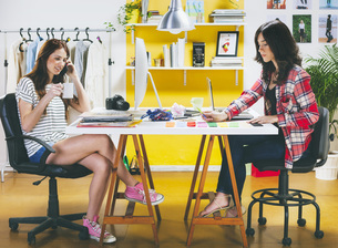 Two female fashion bloggers sitting at desk in the officeの写真素材 [FYI04337917]