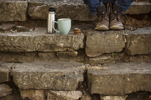 Feet of young man sitting on steps with cup of coffee and thの写真素材 [FYI04337920]