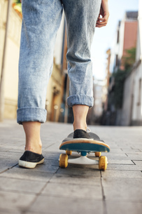 Young female skate boarder on her skateboard, partial viewの写真素材 [FYI04337970]