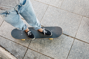 Young female skate boarder standing on her skateboard, partiの写真素材 [FYI04337972]
