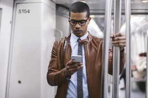 Businessman with smartphone on the subway trainの写真素材 [FYI04337988]