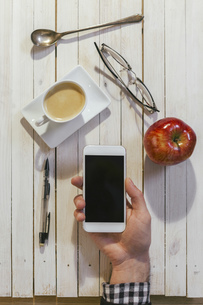 Hands of man with smartphone, cup of coffee, glasses, apple,の写真素材 [FYI04337991]