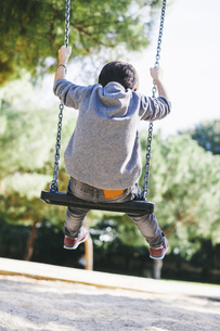 Rear view of boy on a swing at the playgroundの写真素材 [FYI04338016]