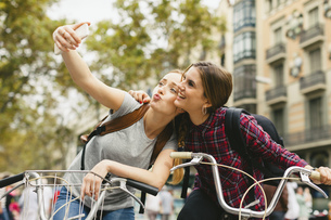 Spain, Barcelona, two young women on bicycles taking a selfiの写真素材 [FYI04338018]