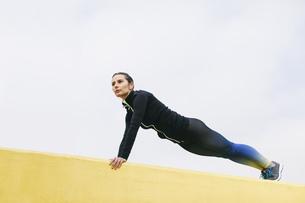 Spain, Barcelona, female jogger on yellow wall, pushupの写真素材 [FYI04338034]