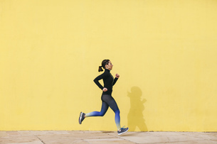 Spain, Barcelona, jogging woman in front of yellow wallの写真素材 [FYI04338035]