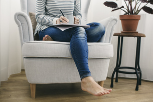 Woman sitting in armchair writing on notepadの写真素材 [FYI04338041]