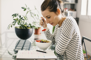 Woman sitting at table with fruit muesli looking at notepadの写真素材 [FYI04338044]