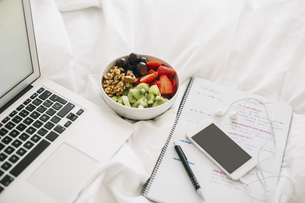 Laptop, notepad, fruit bowl and smartphone with earphones onの写真素材 [FYI04338046]
