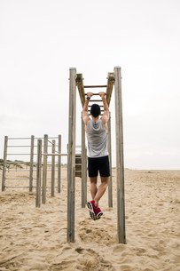 Young man exercising on monkey bars on the beachの写真素材 [FYI04338068]