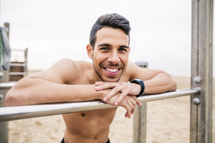 Portrait of smiling athlete on bars on the beachの写真素材 [FYI04338069]