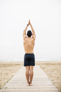 Young man practicing yoga on boardwalk on the beachの写真素材 [FYI04338075]