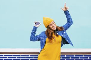 Dancing young woman wearing yellow cap and dressの写真素材 [FYI04338079]