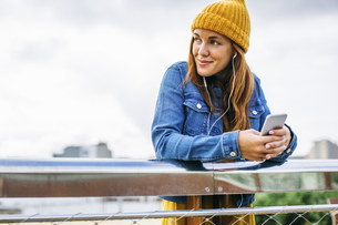 Smiling young woman wearing yellow cap listening music withの写真素材 [FYI04338082]