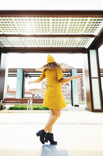 Back view of  dancing young woman wearing yellow clothesの写真素材 [FYI04338085]