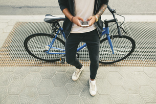 Teenager with a bike in the city, using smartphoneの写真素材 [FYI04338092]