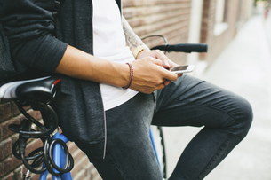 Teenager with a bike in the city, using smartphoneの写真素材 [FYI04338095]