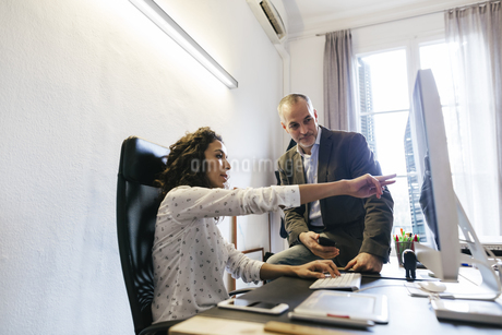 Businessman and woman in office working together on computerの写真素材 [FYI04338100]