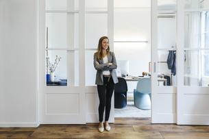 Confident businesswoman standing in officeの写真素材 [FYI04338103]