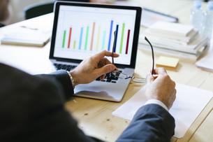 Businessman studying bar chart on laptopの写真素材 [FYI04338112]