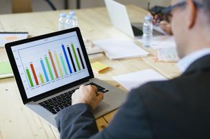 Businessman studying bar chart on laptopの写真素材 [FYI04338113]