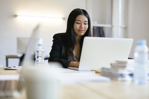 Young Asian woman working in office using laptopの写真素材 [FYI04338119]