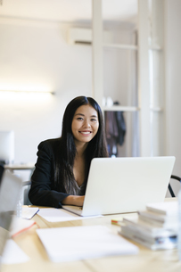 Young Asian woman working in office using laptopの写真素材 [FYI04338120]