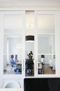 Business people having a team meeting behind glass doorsの写真素材 [FYI04338130]