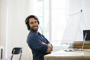 Businessman in office using headphones at deskの写真素材 [FYI04338134]