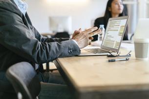 Businessman sitting in meeting, using laptopの写真素材 [FYI04338151]