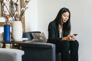 Businesswoman sitting in lounge using smart phoneの写真素材 [FYI04338164]