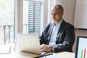 Businessman sitting at desk working on laptopの写真素材 [FYI04338169]
